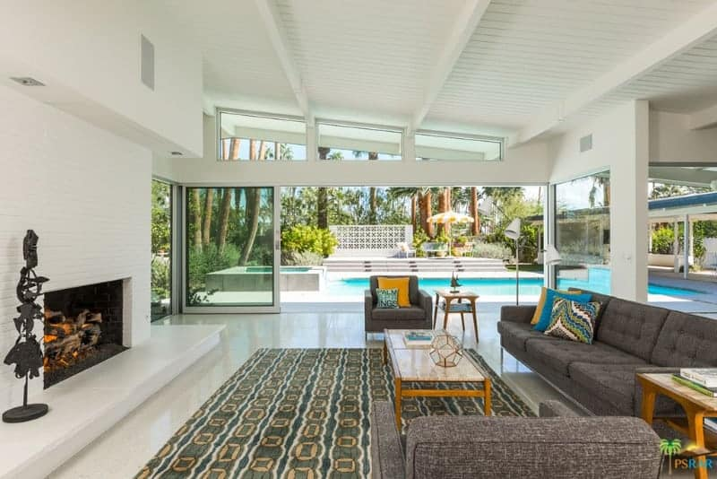 Medium-sized living room with marble tiled flooring and glass slider that opens to the sparkling pool. It includes tufted seats and a wooden coffee table on a green patterned rug facing the fireplace.