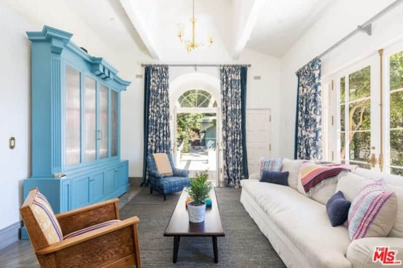 A light blue storage cabinet faces the rectangular coffee table and white skirted sofa filled with fluffy pillows. It is accompanied by mismatched chairs and white framed windows covered in patterned draperies.