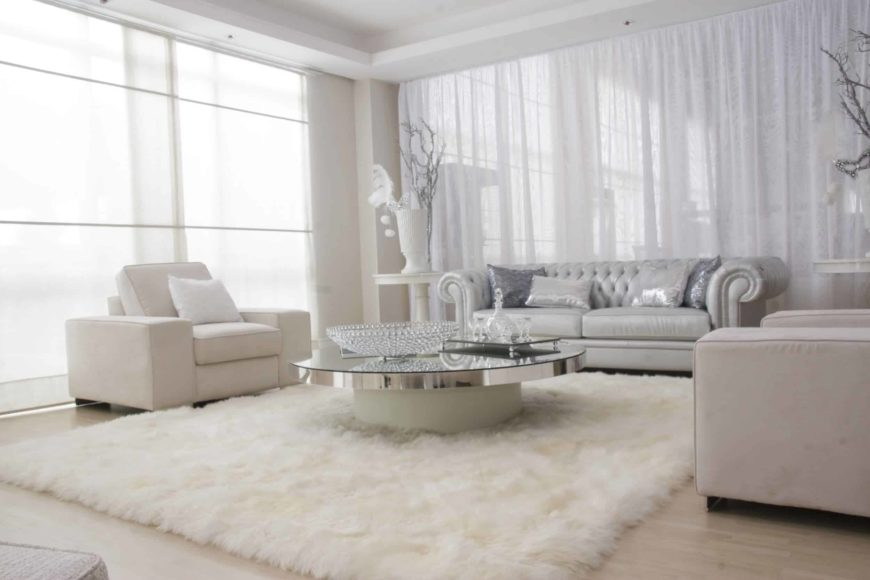 Fabulous living room with classy seats and a round coffee table topped with glass bowl. It sits on a white shaggy rug over the light hardwood flooring.
