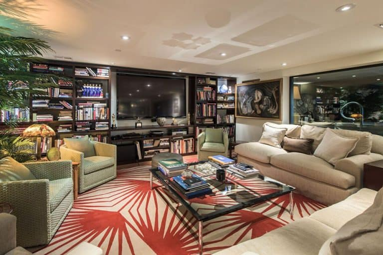 A red patterned rug stands out in this living room with cozy seats and a glass top coffee table facing the wall mount TV surrounded by open shelving.