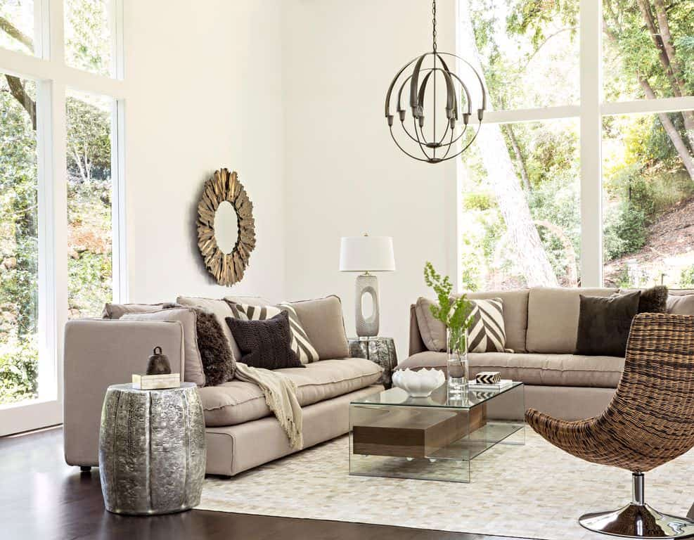 Gray sofas and a wicker chair surround a glass coffee table lighted by a spherical pendant. This room is decorated with a sunburst mirror and a stylish table lamp that sits on a barrel side table.