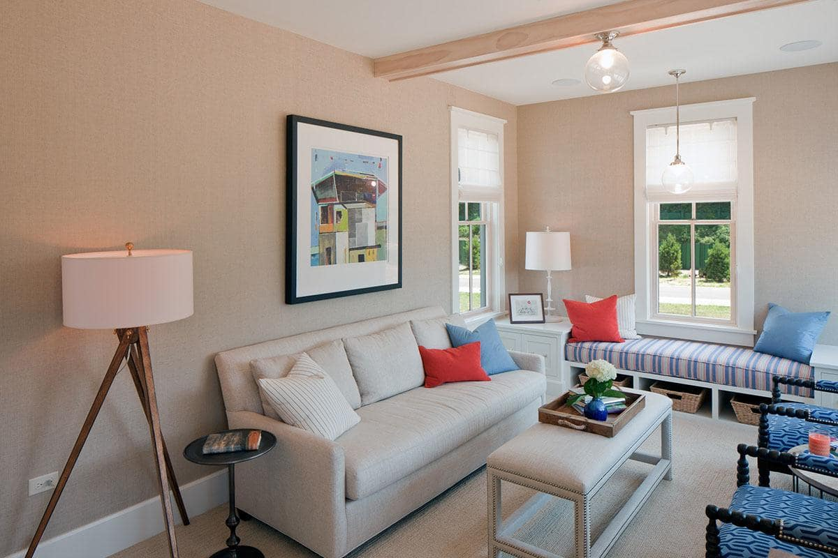 Medium-sized living room with blue patterned armchairs and a gray sofa paired with a cushioned coffee table. It includes lovely wall art and a window seat nook completed with a striped cushion and multi-colored pillows.