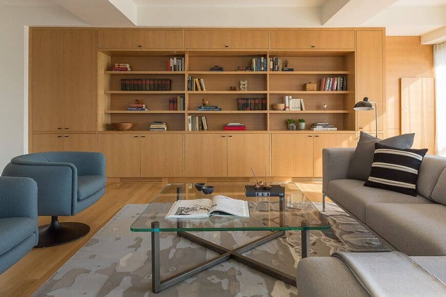 The cozy living room offers sleek seats and a glass top coffee table over a printed area rug. It includes built-in cabinets with open shelving filled with books and decors.