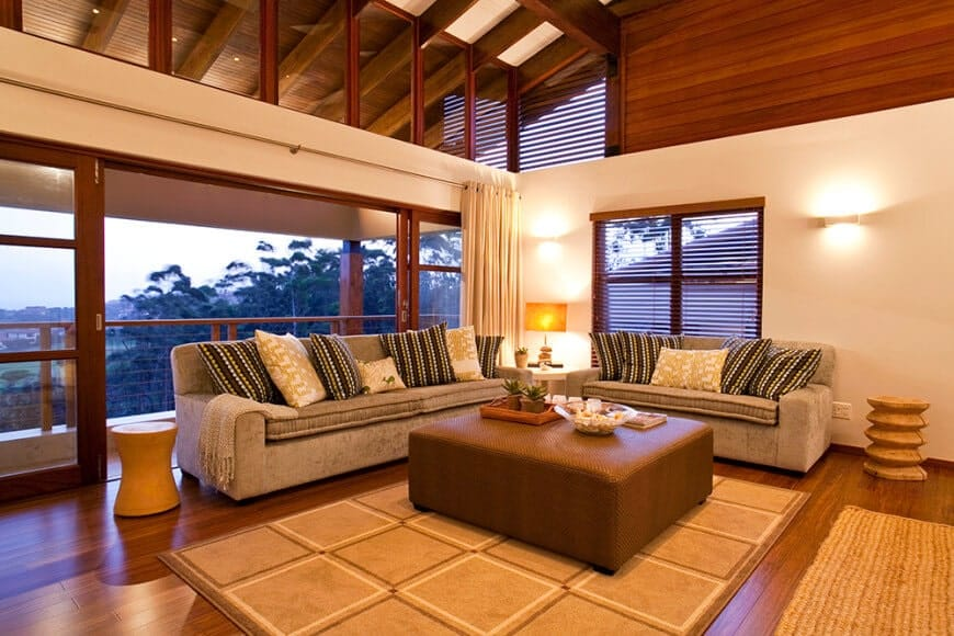 The warm living room offers a brown ottoman and gray sofas accented with printed and striped pillows. It has glass sliders and a rich hardwood flooring topped by tan rugs.