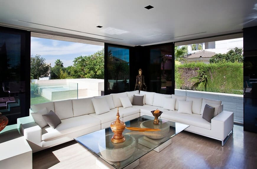 Modern living room with a glass top coffee table and a V-shaped sectional sofa filled with white and gray pillows. It has hardwood flooring and glass sliders leading out to the yard.