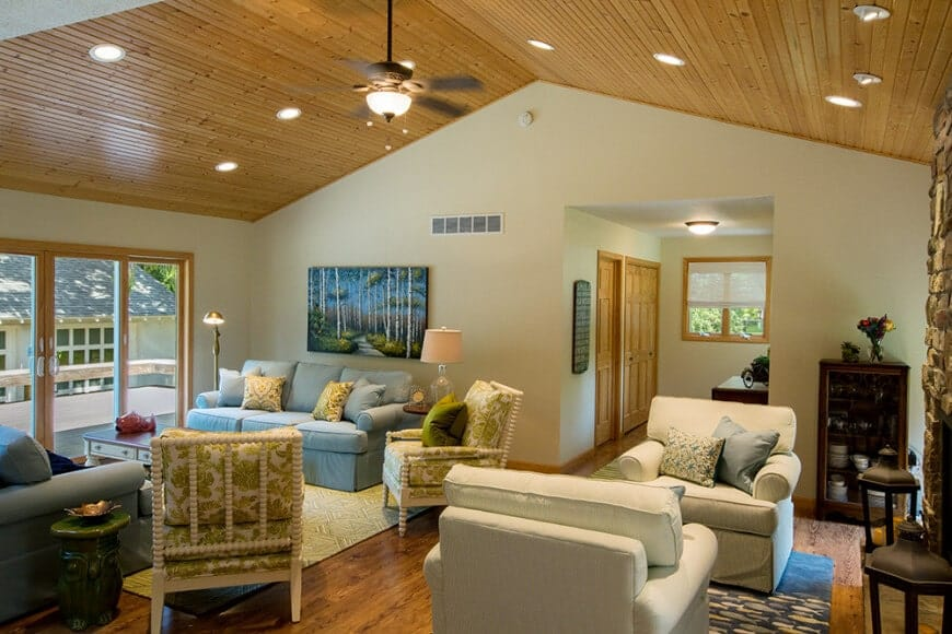 This living room features multiple seating areas and a fireplace fixed on the stone brick pillar. It is illuminated by a flush and recessed lights fitted on the cathedral ceiling clad in wood planks.