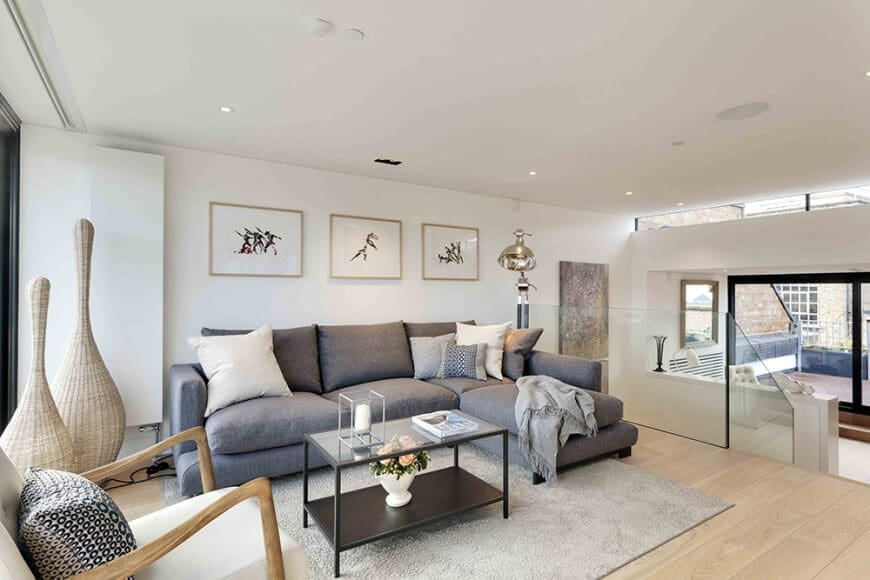 Minimalist wall arts hang above the L-shaped sectional accompanied by white armchair and a metal coffee table over a gray area rug. It has wide plank flooring and a regular ceiling mounted with recessed lights.