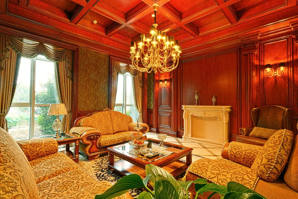 Classy cushioned seats surround a glass top coffee table lighted by a Victorian chandelier that hung from the coffered ceiling. It has marble flooring arranged in a diamond pattern and a wood paneled wall fitted with sconces and a fireplace.