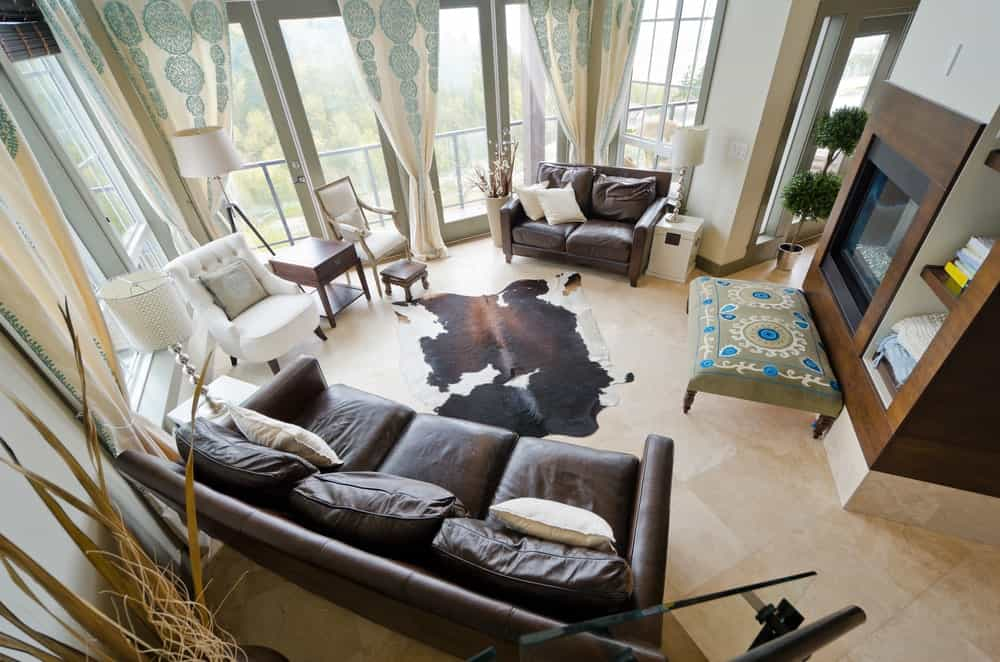 A top view of the medium-sized living room furnished with white chairs and leather sofas along with a patterned ottoman near the glass-enclosed fireplace. It includes charming drapes and a cowhide rug that lays on the limestone flooring.