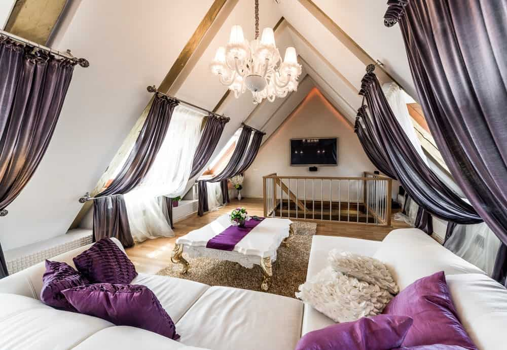 An attic living room illuminated by a white chandelier that hung over the classy coffee table lined with a purple runner. It has a brown shaggy rug and an L-shaped sofa accented with silk and textured pillows.