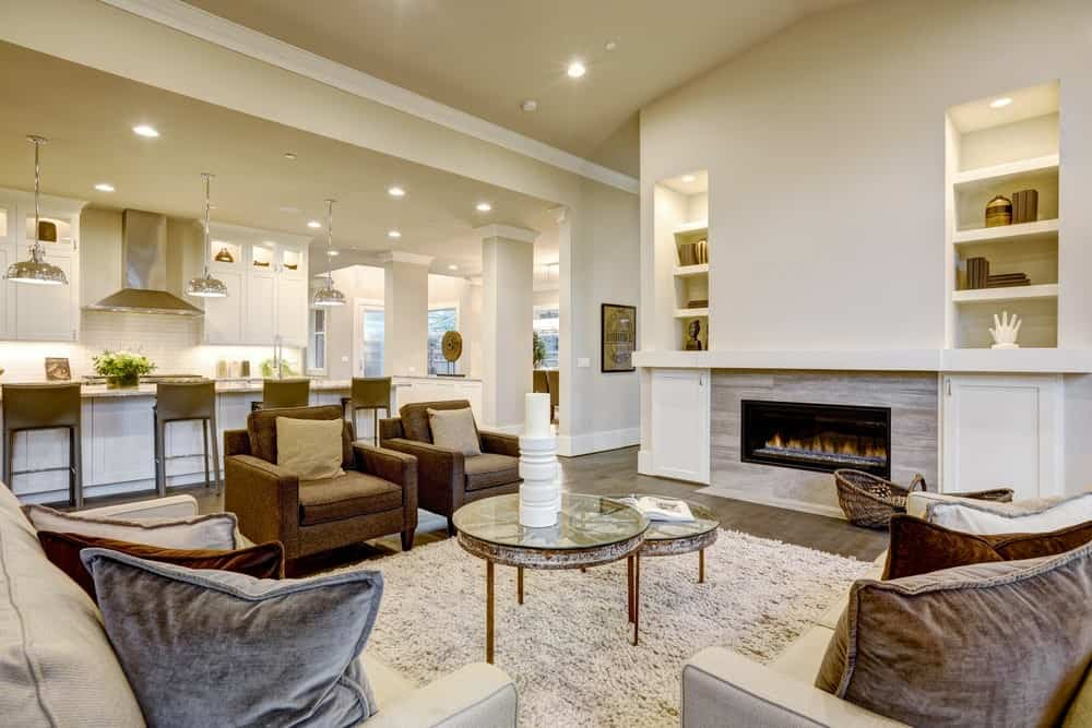 Well-lit living room boasts a fireplace and cozy seats surrounding a modular coffee table over a beige shaggy rug. It has natural hardwood flooring and inset wall niches filled with books and decors.