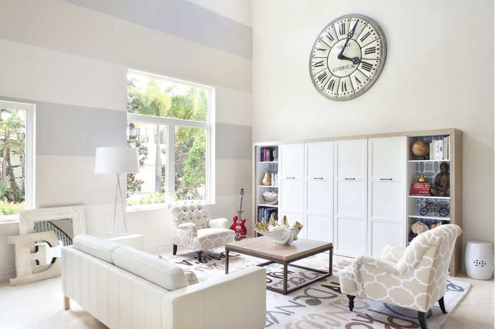 Bright living room decorated with a large wall clock that hung above the white cabinet fitted with open shelvings on the sides. It has patterned tufted chairs and a sleek sofa paired with a metal coffee table that's topped with a decorative bowl.