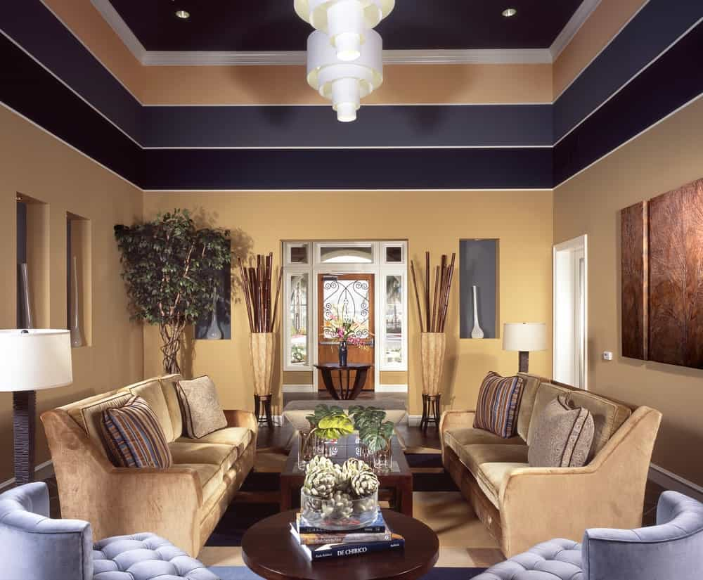 Medium-sized living room with velvet sectionals and wooden coffee tables lighted by a pair of white pendants. It is surrounded by multi-colored upper walls that create an illusion of a multi-layered tray ceiling.