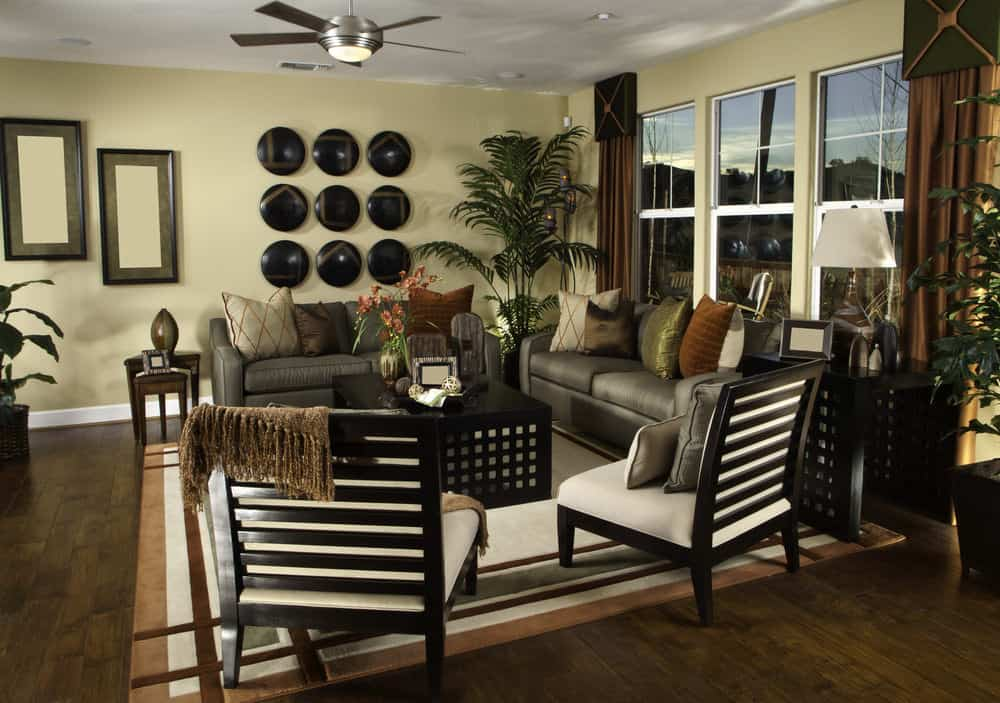 Tropical living room with a chrome ceiling fan and cozy seats surrounding a black coffee table over a bordered area rug. It is decorated with framed and round wall arts mounted on the beige wall.