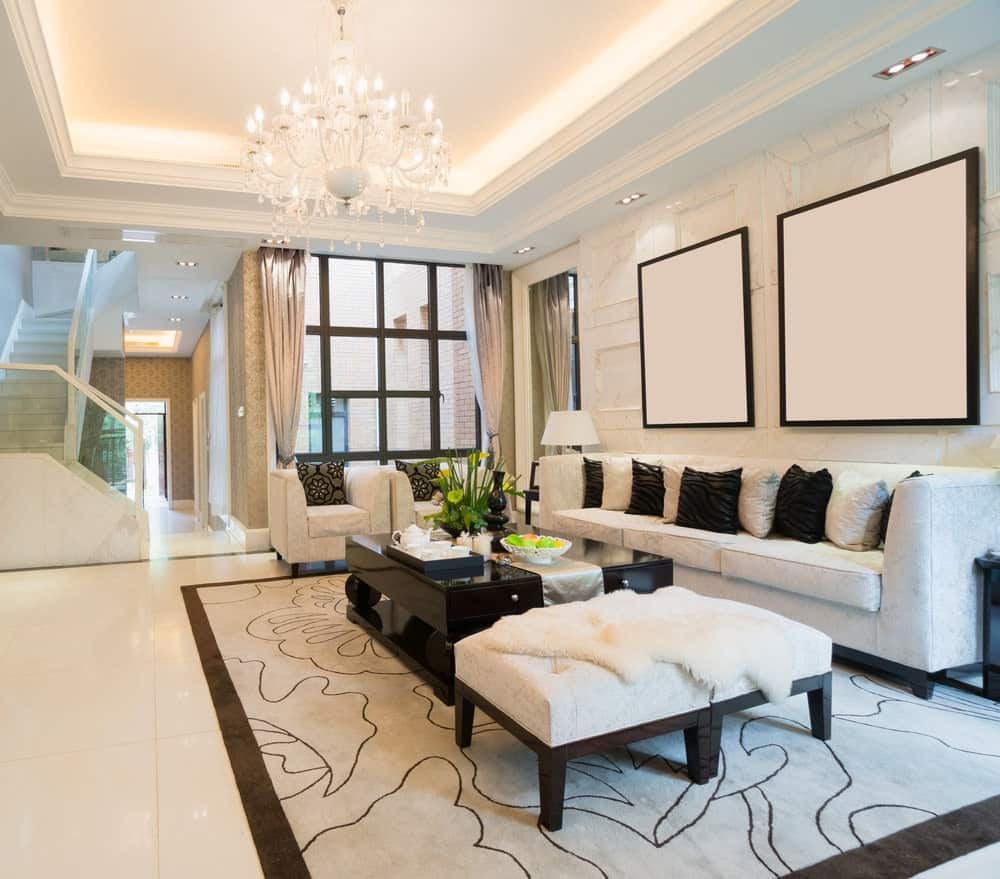 A glamorous chandelier hangs over the black coffee table that sits on a bordered area rug. It is accompanied by gray velvet seats and ottomans topped with a white faux fur blanket.