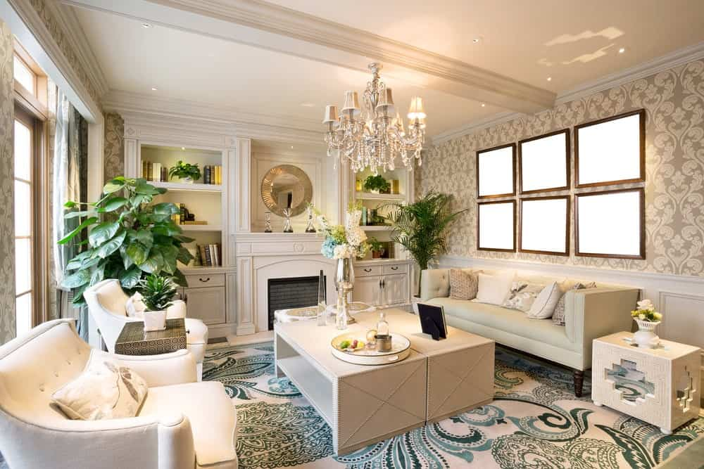 Deluxe living room clad in classy wallpaper and white wainscoting. It has sleek seats and a pair of rectangular coffee tables lighted by a Victorian chandelier.