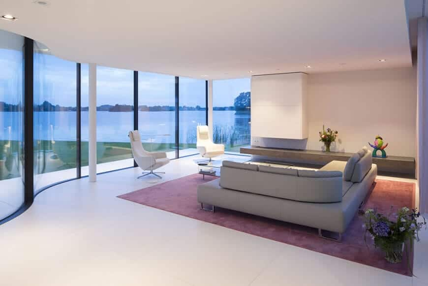 The modern living room offers sleek chairs and a V-shaped sofa over a red area rug. It has white tiled flooring and a panoramic window overlooking a stunning lake view.