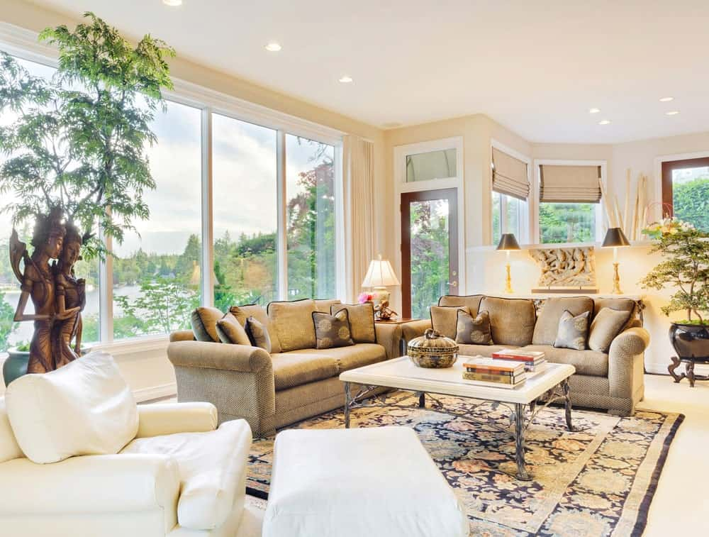 Bright living room with tiled flooring and glass paneled windows overlooking a picturesque view. It has classy seats and a stylish coffee table over a black floral rug.